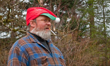 This middle aged Caucasian man with a long beard is wearing a Christmas hat while smoking a cigarette outdoors.  He Stock Photo - 10002123