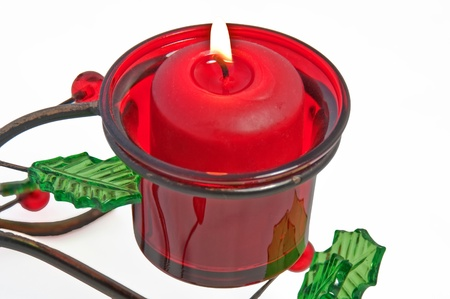votive candle: This red votive candle is lit and burning in a Christmas holder that is metal with glass holly leaves and berries, isolated on a white background.