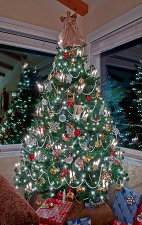 Esta imagen hermosa es una fotograf�a vertical de un interior iluminado y decorado �rbol de Navidad con dos ventanas que reflejan las luces y la decoraci�n, regalos debajo del �rbol y un �ngel en la parte superior. Establecer en la noche con las luces va completar este tradicional ho Foto de archivo