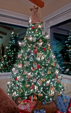 This beautiful stock image is a vertical shot of an indoor lighted and decorated Christmas tree with two windows reflecting the lights and decor, presents under the tree and an angel on top.  Set at night with the lights going complete this traditional ho
