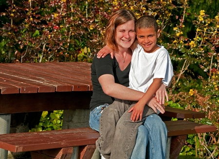 mother on bench: This image is a happy mother and son snuggling together outdoors on a park bench.  Son is 8 years old and bi-racial and is sitting on mom Stock Photo