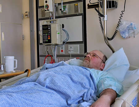 bedside: This image is a middle aged bearded Caucasian man who is in hospital