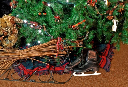 checkered scarf: This holiday still life shows black vintage skates under a lit Christmas tree with a bear to the side, wrought iron decor with sticks, homespun and primitive handmade ornaments decorate the tree as well.  The tree skirt is a classic plaid scarf. Stock Photo