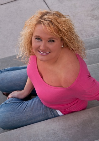 This pretty blond haired middle aged woman is smiling and confident while sitting on stairs.  Vertical image, model is wearing blue jeans and a pink shirt.