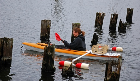 This young Caucasian woman is smiling and happy as she manuvers her kayak with homemade outriggers for stablization through a maze of wooden pilings in the water. photo