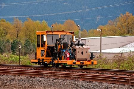 machinery: This stock image shows a single machinery equipment with an unidentified person working on railroad tracks.  Photos taken in early spring with mountains in the background. Stock Photo