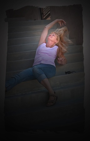 midlife: This middle aged Caucasian woman with long blond hair is relaxing while playing with her hair on stairs.  Image is vertical orientation with ragged edges and viganette borders.  Dramatic lighting also emphasizes her face.