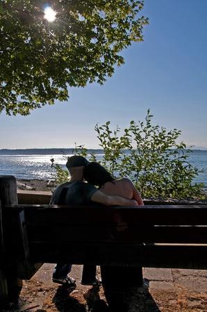 Romantische Paar zittend op bankje bij Beach
