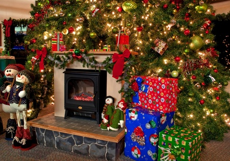 This image is a traditional Christmas hearth scene with a huge decorate Christmas tree with lights and ornaments, gifts and presents piled under the tree and on top of the hearth, with snowmen decoration as well.  Very homey photo.