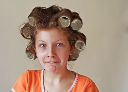 This image is a 9 year old Caucasian girl with green eyes, has her hair in rollers (curlers) and having a humorous facial expression showing lots of apprehensive emotion to this experience.  Shot on a light background. photo