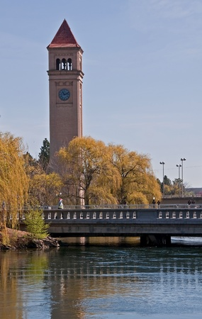 This vertical stock image shows the town of Spokane, WA clock tower in Rivertfront Park in early spring.  The willow trees are still dormant on this lovely day.