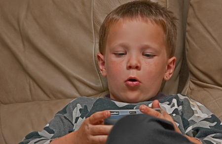 This 5 year old Caucasian boy with freckles is concentrating as he Stock Photo - 11058591