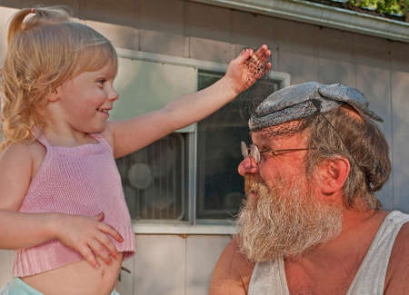 This blond haired, 2 year old toddler girl is playing dress up with grandpa, by putting a vintage hat with a veil on his head and is lifting up the veil.  Playful happy family moment. photo