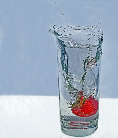 This stock image shows a fresh strawberry splashing into a tall clear glass of sparkling water with water splashes out over the rim.  Lots of light playing in the water droplets of this refreshing, cool drink. photo