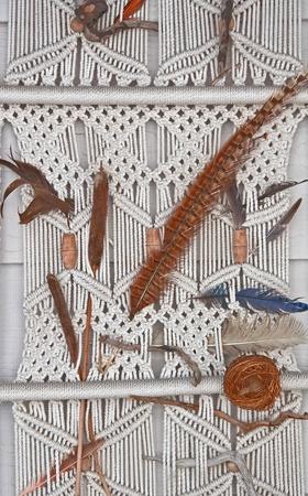 Esta es una parte de un macram� hechos con cuerdas blancas en una pared colgante, con plumas y otros elementos naturales a�adidos para completar este art�culo. Foto de archivo