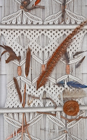 This is a portion of a macrame made with white ropes into a wall hanging, with feathers and other natural elements added to complete this item.