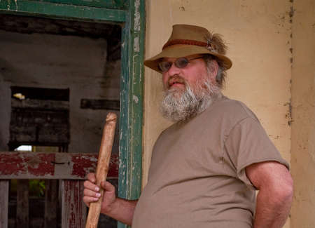 This rugged mountain middle aged man, has a long beard and walking stick.  He Stock Photo