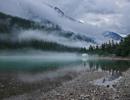 Deze prachtige landschap is een bergmeer met groenblijvende bomen op de berg en wolkenluchten, met zware patronen van mist wisping door. Genomen op Ross Lake, Washington, Amerika. Stockfoto