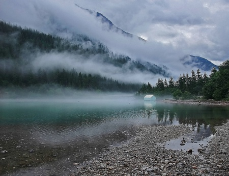 This beautiful landscape is a mountain lake with evergreen trees on the mountain and cloudy skies, with heavy patterns of fog wisping through.  Taken at Ross Lake, Washington, America.