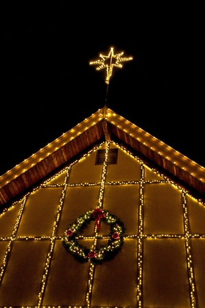 rafters: This vertical holiday stock image is a house rafter area decorated with Christmas lights, a wreath and a star on top against a clear black night.