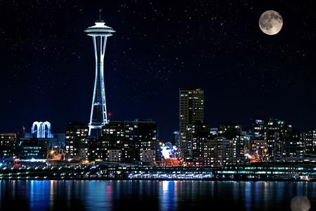 Esta foto es de Seattle, Washington horizonte de la ciudad por la noche. Puget Sound es el primer plano con la luna llena y el cielo estrellado por la noche. Foto de archivo