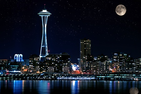 This photo is of Seattle Washington skyline of downtown at night.  Puget Sound is the the foreground with a full moon and starry night sky.