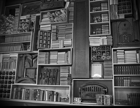 This very large vintage bookcase has antique books, old brown bottles, rolled up maps and other retro objects on it photo