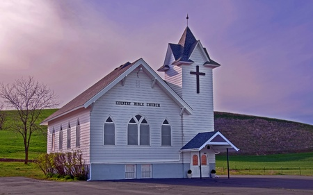 This classic white country church is located in rural Dusty, Washington in Whitman County in the South Eastern part of Washington.  Shot on a spring day with the trees still bare and the lighting warm and dramatic.  Has a classic cross on the front of the Stock Photo