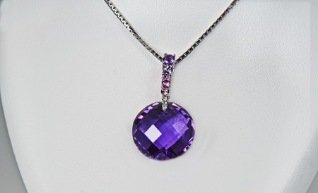 This stock image is a large, round genuine amethyst stone as a pendant on a necklace in fine jewelry, against a white collar display.