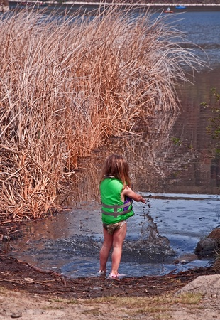 This cute 3 year old Caucasian girl is having great childhood fun  playing in the mud with a mighty splash at the shore of a lake with reeds nearby and fisherman in the background.  She photo