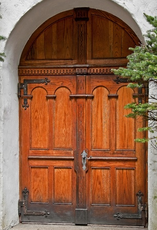 achitectural: This vertical image is beautiful wooden double doors, in a rustic setting with stucco building in an archway.  Achitectural element that is simply gorgeous in it Stock Photo