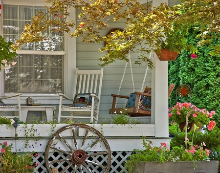 This cute welcoming scene is a detailed area of a home showing a summertime class porch scene with a swing, rocking chair, flowers and hanging baskets and home related pillows.  All objects beckon a person to come and sit awhile.