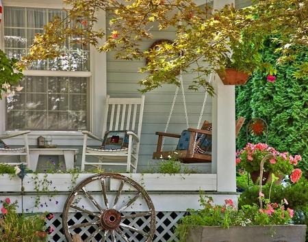 columpio: Esta escena de bienvenida lindo es un �rea de detalle de una casa que muestra una clase de verano escena porche con un columpio, silla mecedora, flores y cestas colgantes y almohadas en casa relacionados. Todos los objetos atraen a una persona que venga a sentarse un rato.