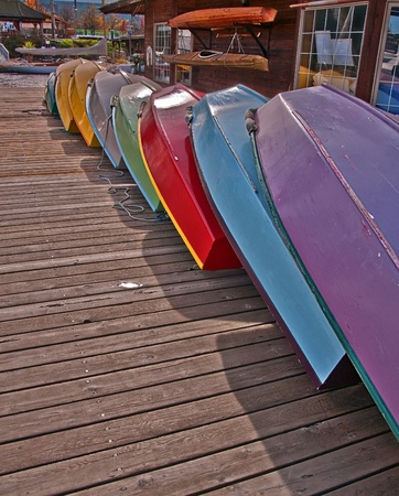 96075e530d2 This vertical stock image shows a row of colorful rowboats with the bottoms  up