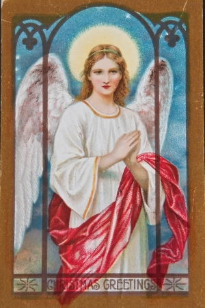 retro christmas: USA - CIRCA 1900 - This aged vintage postcard is showing signs of wear, in a Christmas holiday angel with words Christmas Greetings
