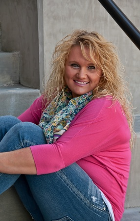 This middle aged pretty Caucasian woman is sitting from a side view and smiling directly into the camera in a warm, engaging expression.  Model has long blond hair, is wearing a pink sweater and floral scarf, and blue jeans. photo