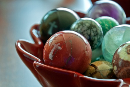 home accent: This stock image shows two white crosses reflected in a bowl of large, glass marbles.  Background intentionally blurred for artistic effect. Stock Photo