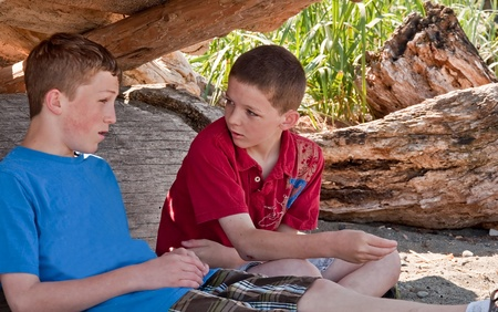 11 year old: These two Caucasian brothers are talking in their makeshift fort they made at a beach.  One is 13 the other 11 year old boys, waist up, side view horizontal image of family together. Stock Photo