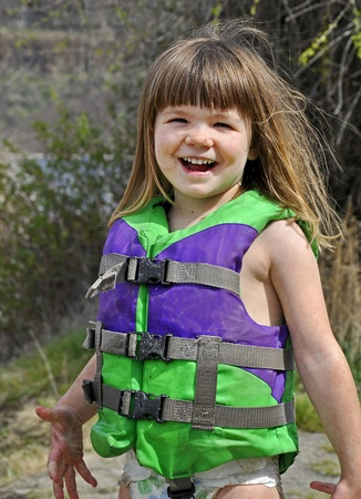 lifevest: This cute 3 year old Caucasian girl is smiling and happy while playing outdoors.  Stock Photo