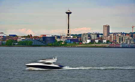 A speedboat is rushing by in the foreground of this cityscape of a skyline of Seattle, Washington, in King County.  Space needle monument is in the image. photo