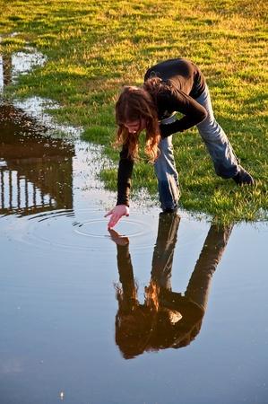 Este pelo largo pre-adolescente chica de raza cauc�sica est� haciendo ondas en el agua al tocar un agua todav�a con la mano. Iluminaci�n espectacular hacen de este una bella imagen.