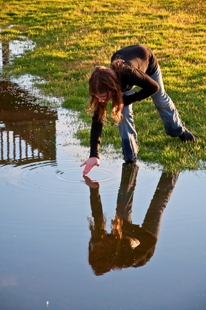 with reflection: This long haired pre-teen Caucasian girl is making ripples in water by touching a still water with her hand.  Dramatic lighting makes this a beautiful image.