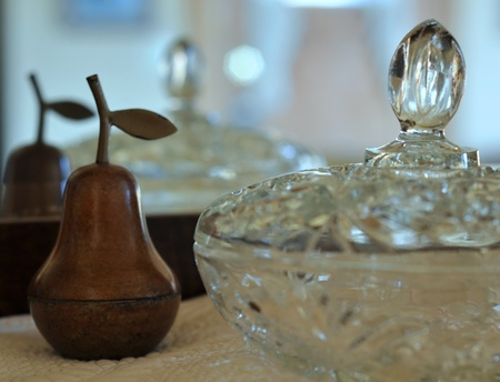 inanimate: This still life is a wooden pear and a crystal dish of interior decor objects, set with a mirror reflecting in the background with lots of light with these home related items. Stock Photo