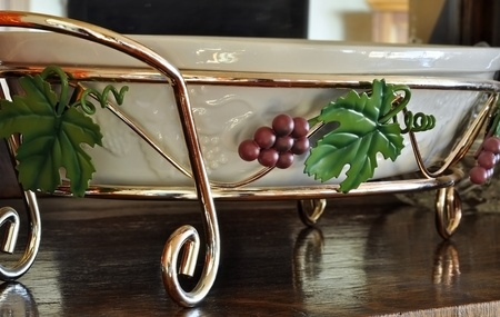 inanimate: This stock image is a grape metal platter dish holder of a home related object, sitting on a wooden surface.  The platter is an off white ceramic dish.  Home interior decor item.