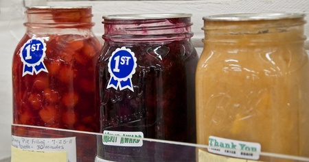Three jars of various homemade fruit pie filling with first place ribbons are in this home canned competition at a county fair.