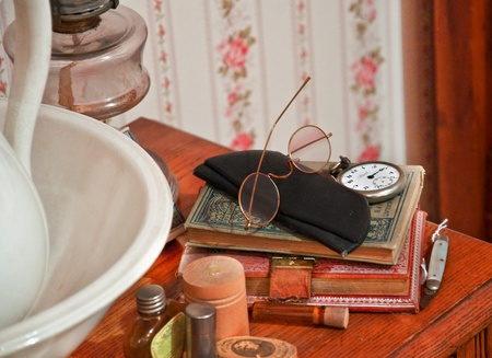 This stock image shows vintage reading glasses on top of retro books, a pocket watch and other toiletry antique objects. 写真素材