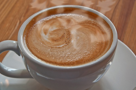 This is a macro stock image of a hot cup of latte coffee in a glass white cup and saucer.  The latte is poured white decorative patterns in the beverage. photo