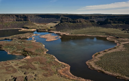 This landscape is a stunning canyon with many lakes below, across of which can be seen mesas, cliffs and bluffs.  Boats can be seen below on the water as well.  Taken of Dry Falls in Grant County, Washington, USA. photo