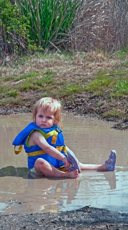 This cute 18 month old Caucasian toddler girl is sitting in her diaper and life vest in a mud puddle and playing as she
