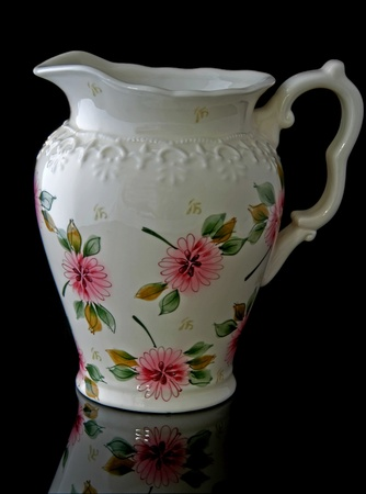 cream colored: This stock image is a cream colored, floral water pitcher for home decor accent use, isolated on a black background with a beautiful reflected image in the foreground.